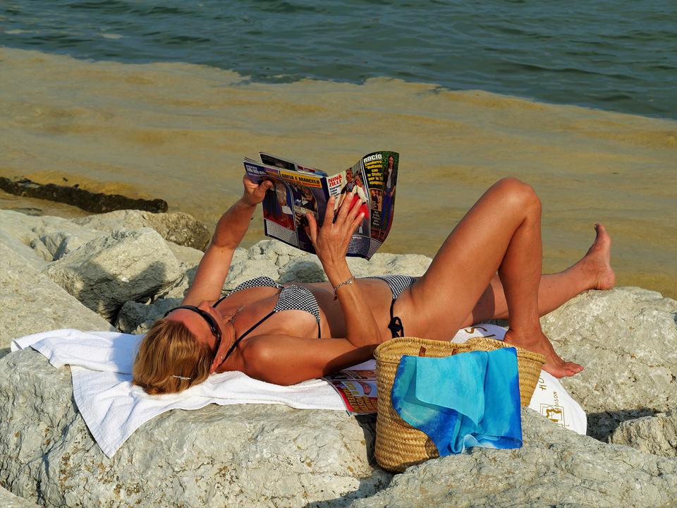 SECONDA CLASS IdeaVisiva - Angelo De Maio– La foto rappresenta una bella distrazione e spiega che sono addirittura due, una l'aria inequivocabile della rilassatezza di una vacanza marina con tutti i suoi crismi identificativi, l'altra la lettura di una ri