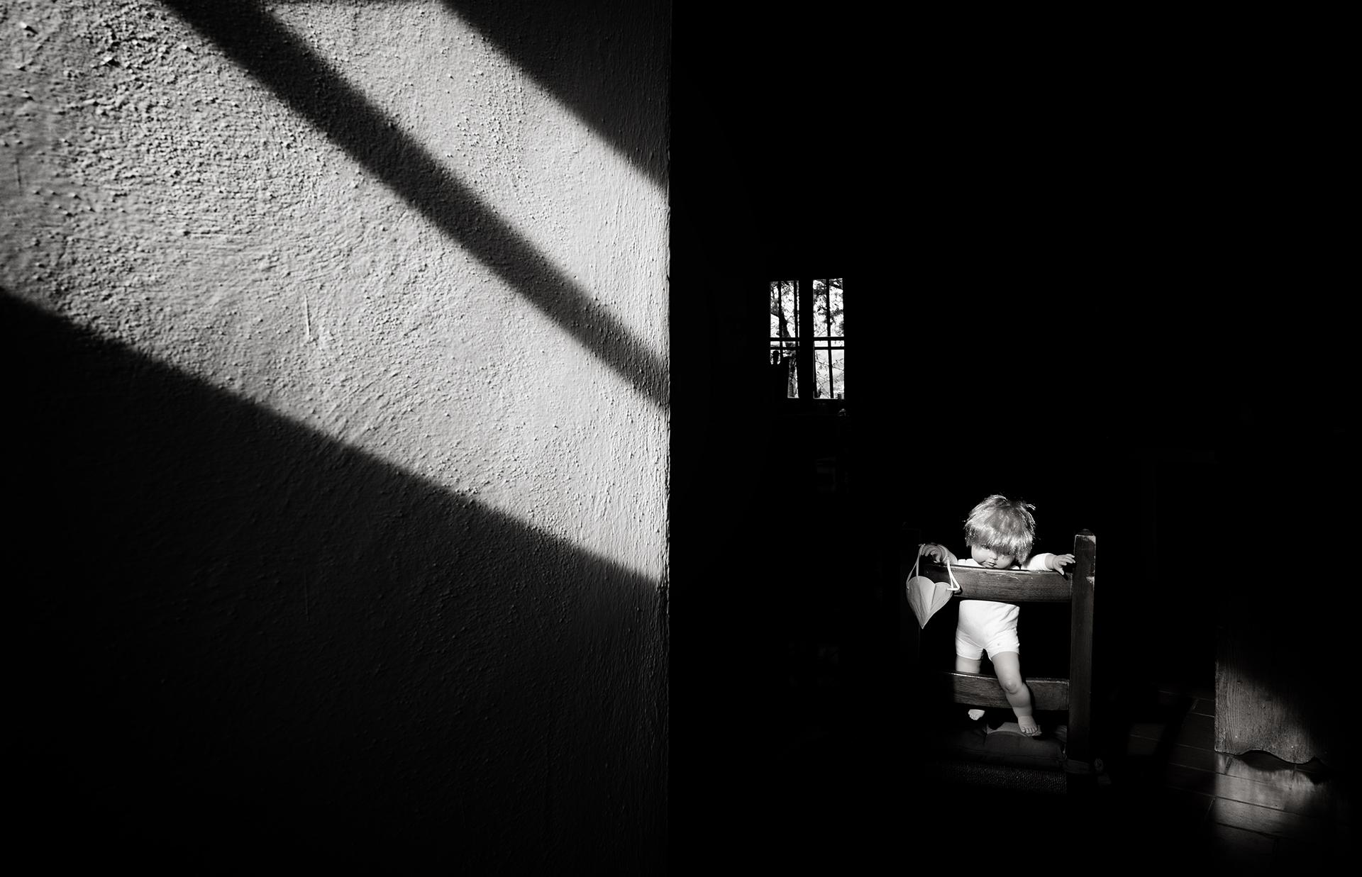 Foto n° 12 QUINTA– PHOTO CLUB MUGELLOLUCA MERCATALI  Un po' di luce entra, la speranza del ritornare fuori la rappresenta la finestra, un bambolotto simboleggia la forzata reclusione, se così si può dire. Gli elementi che compaiono non sono in gran numer